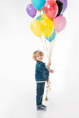 smiling adorable boy with bundle of balloons isolated on white