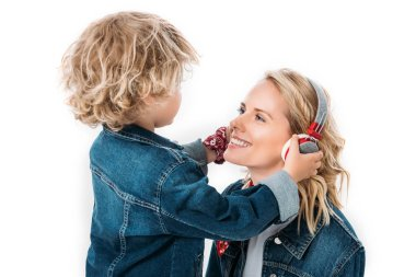 son wearing headphones on mother to listen to music isolated on white