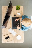 overhead view of female freelancer drinking coffee working on graphic tablet at table with smartphone and computer at home office
