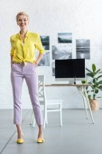Fotografie stylish smiling businesswoman with hands in pockets looking at camera at office