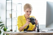 smiling female photographer looking at camera screen at table with computer