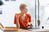 Fotografia smiling female freelancer eating pizza and drawing on graphic tablet at home office