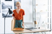 Fotografia happy female freelancer opening pizza box at table with graphic tablet at home office