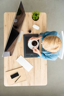 overhead view of female freelancer holding cup of coffee at table with graphic tablet, smartphone and computer at home office