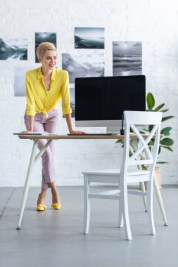 stylish young businesswoman standing near table with computer at office