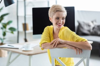 selective focus of smiling businesswoman sitting near table with computer at office