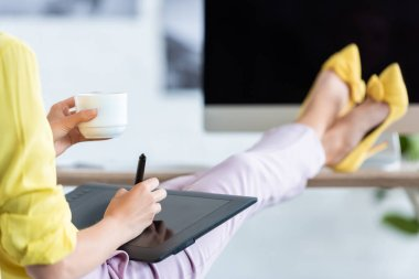 cropped image of female freelancer drinking coffee and using graphic tablet at table with computer at home office