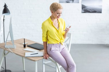 stylish smiling female freelancer using smartphone near table with graphic tablet and computer at home office