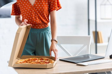 cropped image of female freelancer opening pizza box at table with graphic tablet and computer