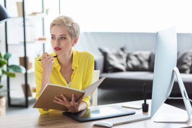 pensive female freelancer holding textbook and sitting at table with computer and graphic tablet