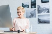 Fotografie happy female freelancer drawing on graphic tablet at table in home office