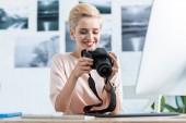 Fotografie šťastné ženy fotograf při pohledu na obrazovku fotoaparátu se u stolu s počítačem v domácí kanceláři
