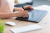 oříznutý obraz ženské nezávislý na grafický tablet u stolu v domácí kanceláři