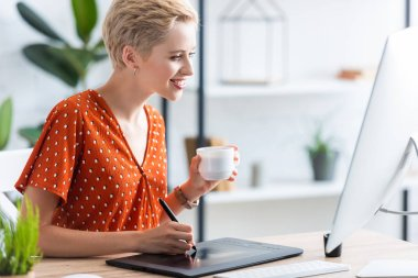 side view of happy female freelancer with coffee cup drawing on graphic tablet at table with computer