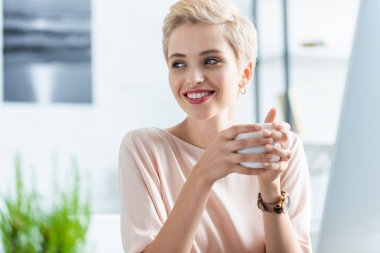 portrait of woman holding cup of coffee and looking away