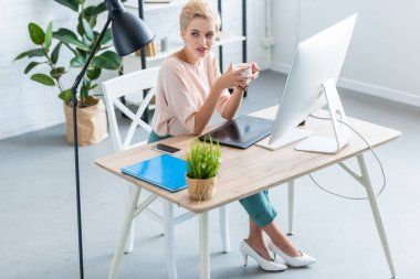 high angle view of female freelancer holding cup of coffee at table with graphic tablet and computer in home office