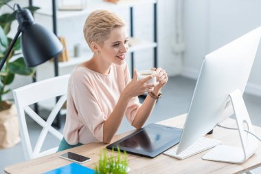 smiling female freelancer drinking coffee at table with graphic tablet and computer in home office
