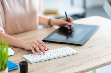 cropped image of female freelancer drawing on graphic tablet at table with computer in home office