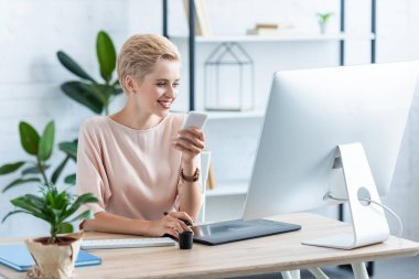 smiling female freelancer holding smartphone at table with graphic tablet and computer in home office