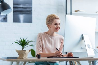 smiling female freelancer drawing on graphic tablet at table with computer