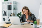 beautiful businesswoman using laptop and writing something to notebook in office