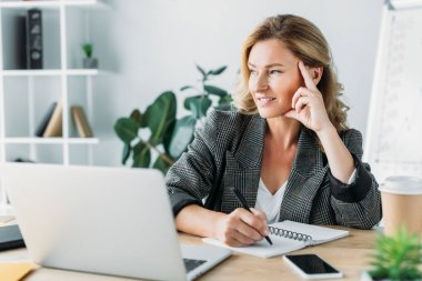pensive attractive businesswoman sitting at table with laptop and notebook in office