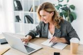 vonzó üzletasszony használ laptop és írásban valami notebook iroda