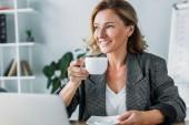 atraktivní podnikatelka posezení s šálkem kávy v kanceláři u stolu a hledat dál