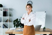 attractive businesswoman standing with crossed arms in office