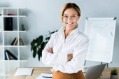 Fotografie beautiful businesswoman standing with crossed arms in office