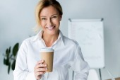 Photo smiling attractive businesswoman holding disposable coffee cup in office and looking at camera