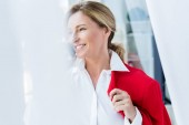 Photo smiling attractive businesswoman holding red jacket and talking by smartphone in office