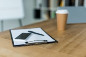 smartphone and disposable coffee cup with clipboard on wooden table in office