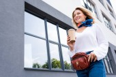 low angle view of attractive woman walking with disposable coffee cup on street