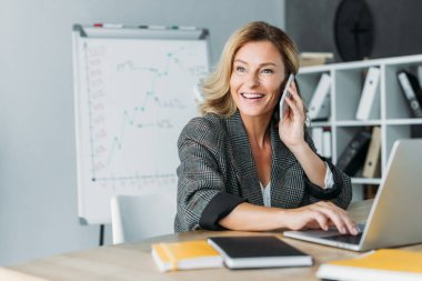 smiling beautiful businesswoman talking by smartphone in office and looking away