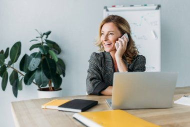 smiling beautiful businesswoman talking by smartphone in office