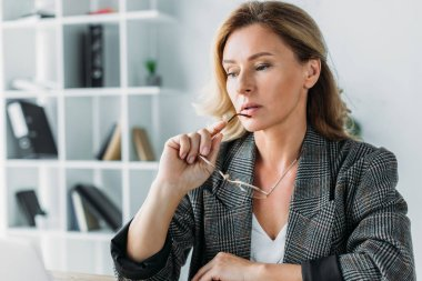 pensive attractive businesswoman biting glasses in office