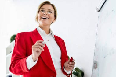 low angle view of attractive businesswoman in red jacket standing near flipchart in office