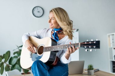 happy attractive businesswoman playing acoustic guitar in office