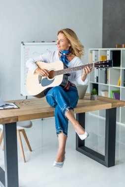 smiling attractive businesswoman playing acoustic guitar in office