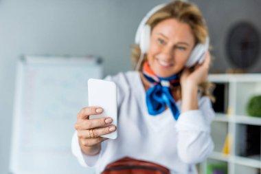 happy attractive businesswoman in headphones taking selfie with smartphone in office