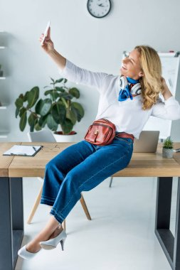 attractive businesswoman sitting on table in office and taking selfie with smartphone
