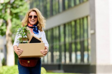 smiling attractive woman holding paper box with office stuff on street