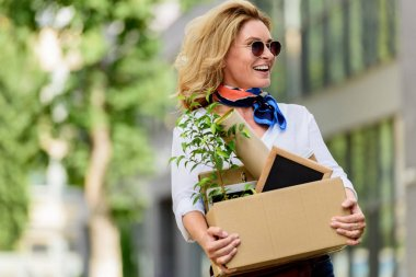 happy attractive woman holding paper box with office stuff on street