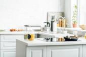interiér prázdné moderní bílá kuchyně s různými předměty na stůl