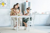 beautiful young family eating breakfast together at kitchen