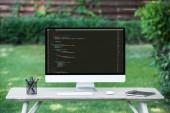 Selektivní fokus počítačového monitoru s programovací kód jazyka v tabulce venku