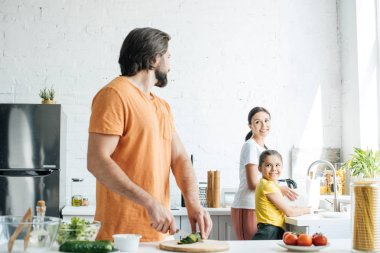 attractive young father cutting cucumber for salad while his wife and daughter washing dishes at kitchen