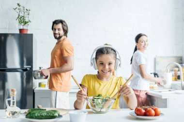 smiling little girl in headphones preparing salad while her parents standing blurred on background at kitchen