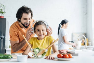 smiling father and happy daughter in headphones cooking together while mother washing dishes blurred on background at kitchen